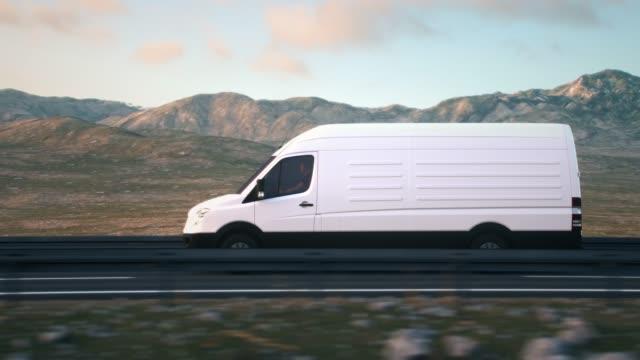 weißer lieferwagen, der auf einer wüstenstraße in den sonnenuntergang fährt - seitenansicht stock-videos und b-roll-filmmaterial
