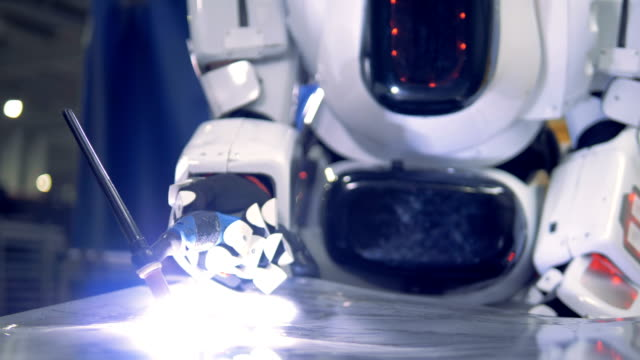 white droid welds on a metal sheet, close up. - rivoluzione industriale video stock e b–roll