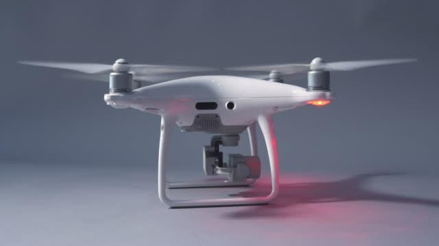 vídeos de stock, filmes e b-roll de o drone branco começa a voar. - quadricóptero