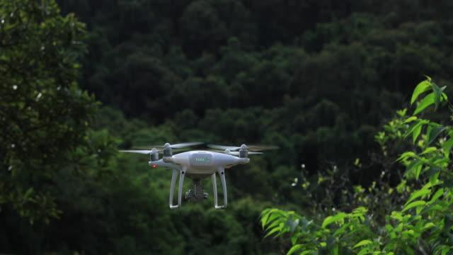 熱帯林を飛ぶカメラ付きの白いドローン - コントロール点の映像素材/bロール