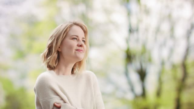 White female in cozy sweater outdoors in sunny green surroundings White female in cozy sweater outdoors in sunny green surroundings mental health stock videos & royalty-free footage