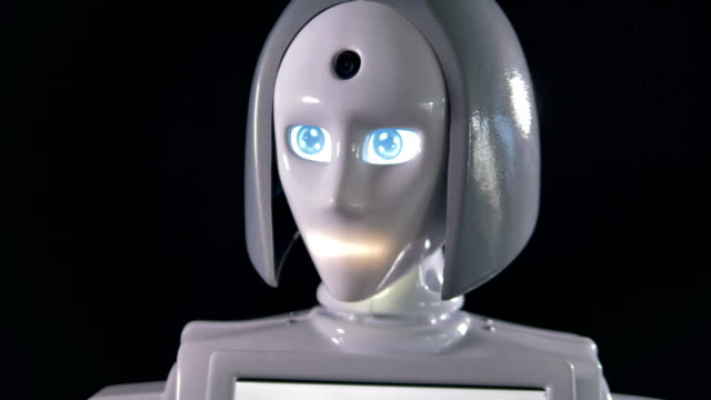 A white female robot moving its eyes. video