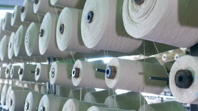 white fiber spooling on bobbins, placed on racks at a factory. - cilindro video stock e b–roll