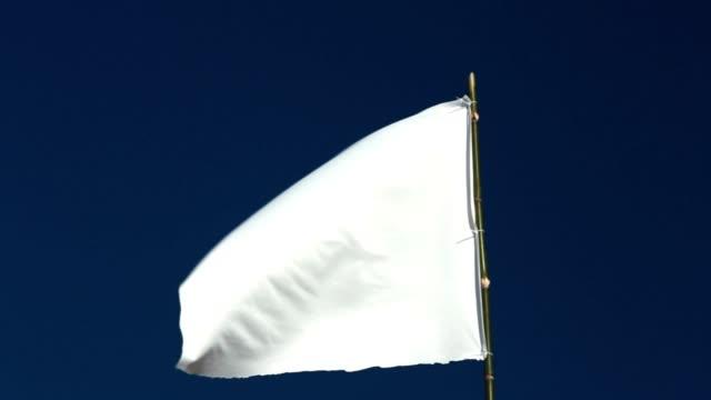 White flag waving in the blue sky