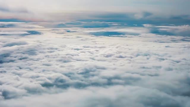 vidéos et rushes de nuages pelucheux blancs dans le ciel bleu, vue supérieure. regardant par la fenêtre d'avion d'avion - glisser