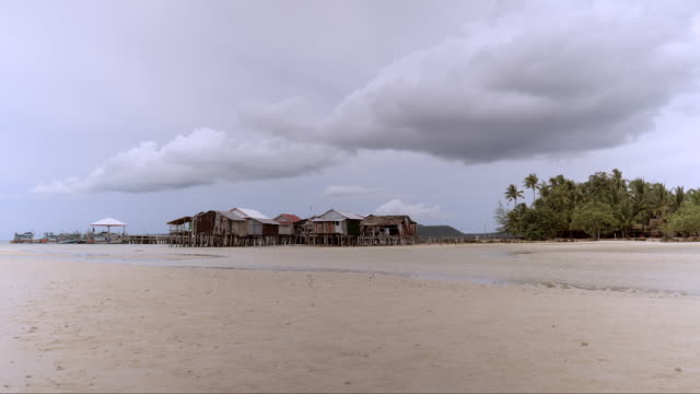 white fluffy rain clouds developing over fishing village and wooden pier on the sand beach