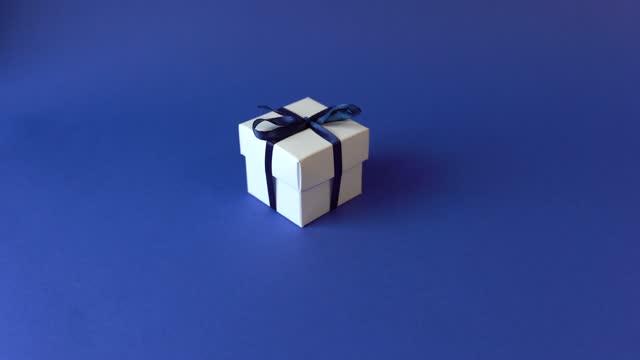 stockvideo's en b-roll-footage met witte gift box met klassieke blauwe lint op blauwe oppervlak. - birthday gift voucher