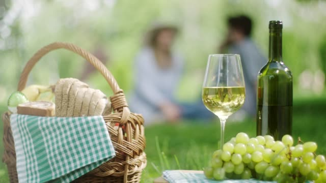 white grape and bottle of white wine with romantic couple in background in public park - uva riesling bianco video stock e b–roll