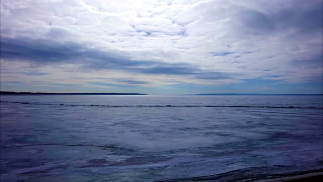 white gray clouds quickly floating over a large pond. the reservoir is covered with a loose spring ice. piercing rays of the sun glisten on the ice. the wind blows stronger cold. spring cloudy day. time  lapse. - pościć filmów i materiałów b-roll