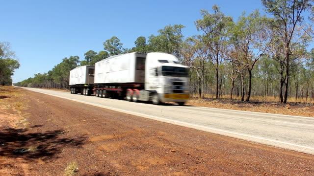 weiße lkw mit zwei anhängern vorbei an leeren straße im outback australien - straßenfracht stock-videos und b-roll-filmmaterial