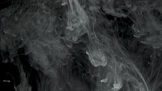 White Ink Effect In Water Filmed On Black Background Stock
