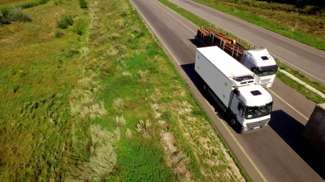 A white isothermal van is moving along the highway Aerial view of a white isothermal van is moving along the highway. On the side of the van there are markers for tracking car transporter stock videos & royalty-free footage