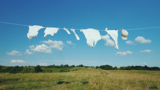 biała pościel wysycha na linie w malowniczym miejscu - pranie filmów i materiałów b-roll