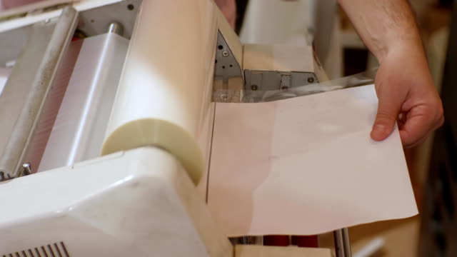 white male working with roll laminator - lithograph stock videos & royalty-free footage
