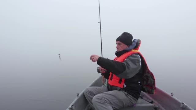 weißer mann fischt von einem boot im dichten nebel auf see in finnland - fischköder stock-videos und b-roll-filmmaterial