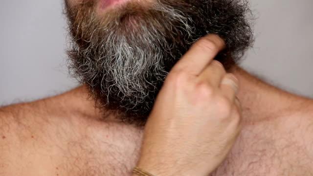 bianco uomo si prende cura dei suoi lussureggianti barba e baffi - lungo video stock e b–roll