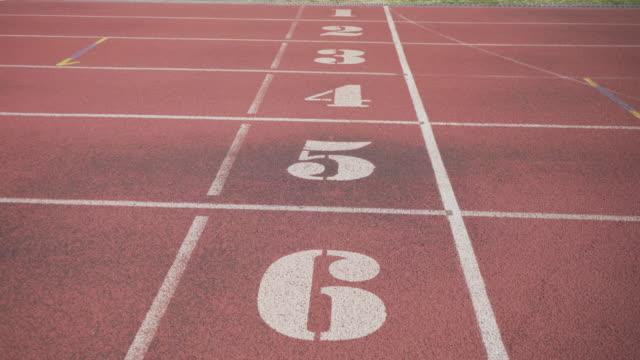 marcature bianche sui sedili dello stadio del tapis roulant di partenza rosso con numeri. - atletico video stock e b–roll