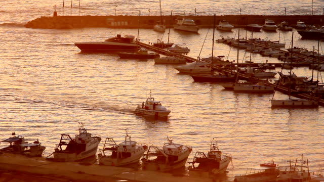bianco di barca a motore di arrivo al porto di santa maria di leuca al tramonto - lecce video stock e b–roll