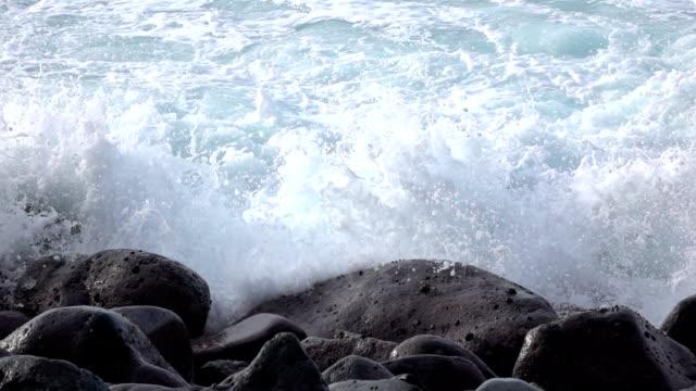 vidéos et rushes de ralenti close up: vagues de l'océan blanc frapper et les éclaboussures sur les roches volcaniques - roc