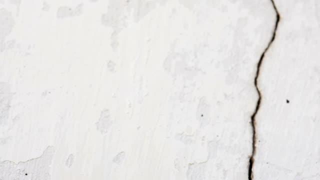 vídeos de stock e filmes b-roll de white old building wall with a crack - rachado
