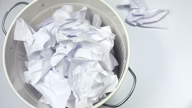 White paper falling into the garbage can video