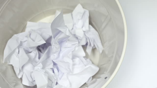 White paper falling into the trash can - close up video