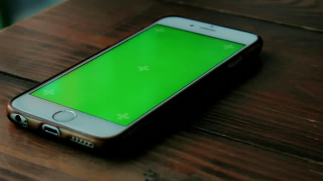 vídeos de stock e filmes b-roll de white phone with a green screen is on a dark brown wooden table in a cafe - table