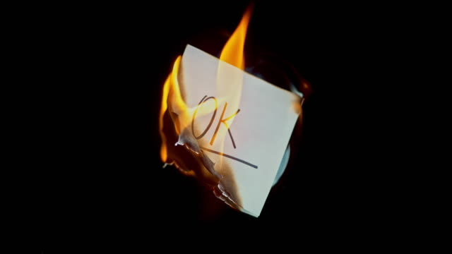 SLO MO LD White piece of paper with the inscription 'OK' burning in flames