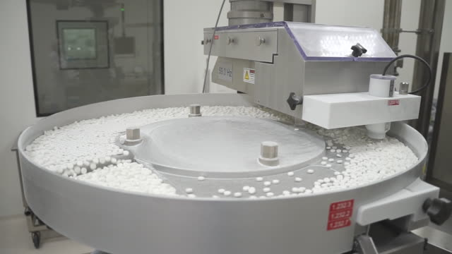 vídeos de stock e filmes b-roll de white pills move on automatic production line at modern pharmaceutical factory - comprimido