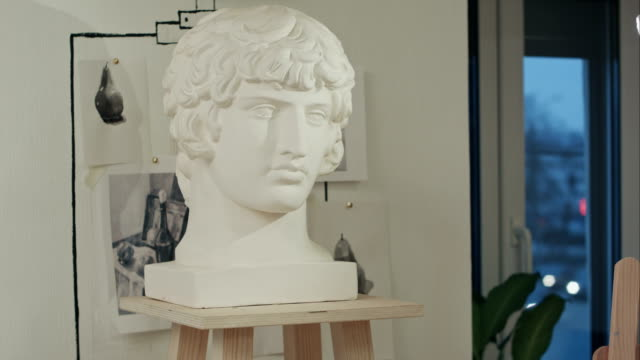 White plaster bust sculpture portrait of a young man in art studio video