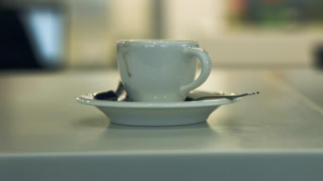 weiße porzellan kaffeetasse auf dem tisch - kaffeetasse stock-videos und b-roll-filmmaterial