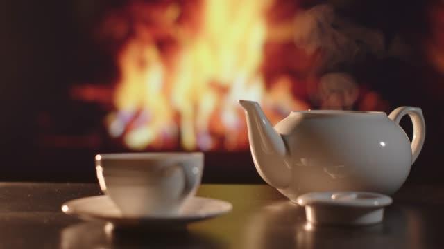 vídeos de stock e filmes b-roll de white porcelain teapot infront of a fireplace - coffee table
