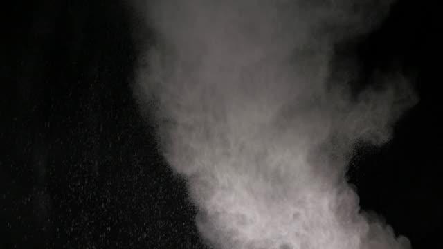 weiße pulverwolke fallen auf schwarzem hintergrund - kreide weiss stock-videos und b-roll-filmmaterial