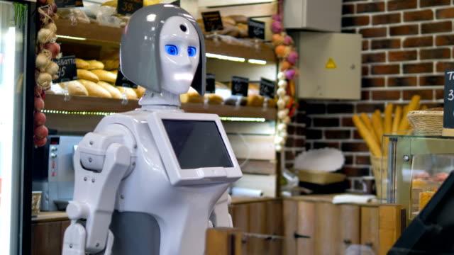 白いロボットは、パン屋さんのカウンターで働いています。 ビデオ