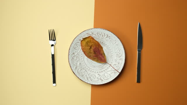 white round plate, knife with fork on brown background, female hand puts dry yellow leaf into plate
