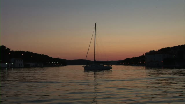 White sailboat docked in a bay video