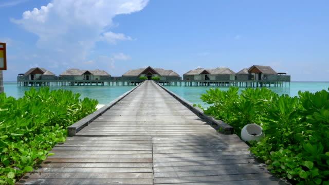 白砂のビーチフロントに建つ水上ヴィラは、エキゾチックなモルディブで - ヴィラ点の映像素材/bロール