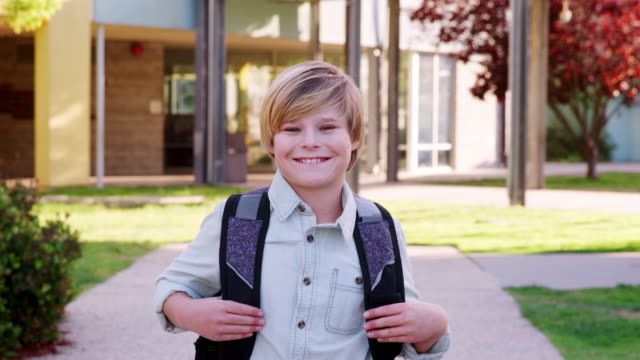 white schoolboy walking to camera outside school building - scolaro video stock e b–roll