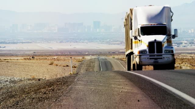 vídeos de stock, filmes e b-roll de um caminhão branco semi rígidos longe o skyline de las vegas na rodovia 604 - carregamento atividade