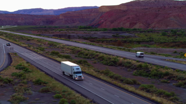 White Semi-truck on Interstate 70 Cutting Through Utah Landscape Drone shot of white truck on freeway cutting through Utah landscape at sunset. semi truck stock videos & royalty-free footage