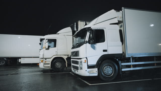 white semi-trucks with cargo trailer drives standing on overnight parking place. drivers resting at night on the overnight parking lot. arc shot - caravan stock videos & royalty-free footage