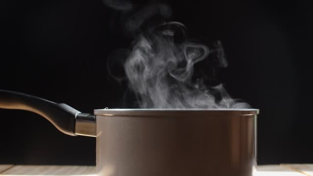 white smoke and steam effect from hot pot on black background. - pentola video stock e b–roll