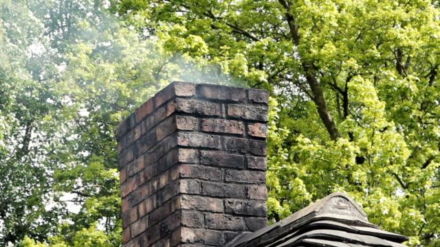 孤独なコテージで石の煙突から白い煙が流れます - 田舎のライフスタイル点の映像素材/bロール