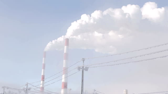 White smoke from industrial chimney on a light background of blue sky video