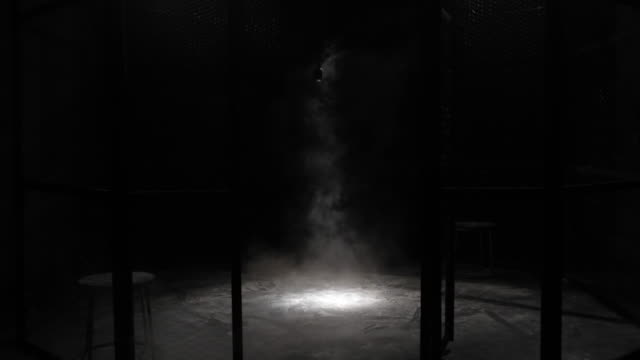 White smoke Projection in a metal grilles cage, circular MMA boxing ring, in a dark studio with a Spotlight or light shower. Show with Vintage microphone. Tracking out. Smoke coming from the ground.