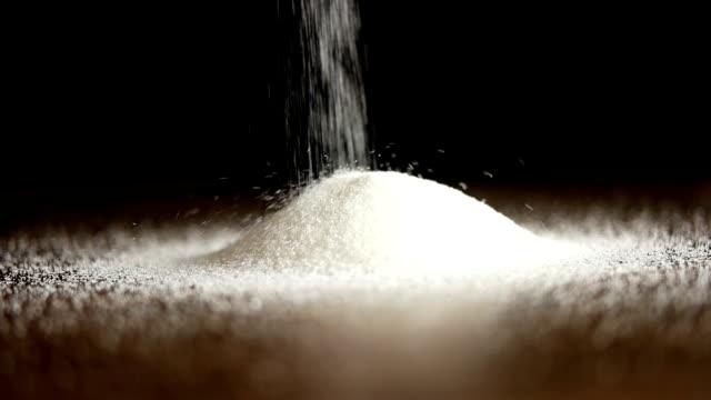 weißer zucker auf schwarzem hintergrund gegossen - gemahlen stock-videos und b-roll-filmmaterial