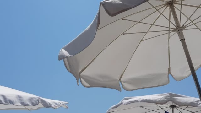 white sunshades parasols moving in the summer wind in front of the clear blue sky - opalenizna filmów i materiałów b-roll