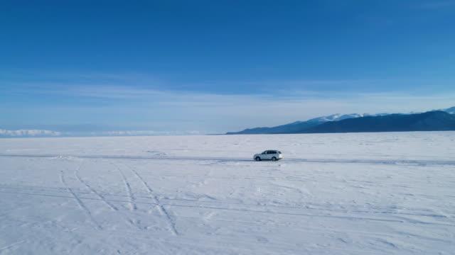 vídeos de stock e filmes b-roll de white suv car driving along empty snow covered surface of lake baikal. - lago baikal