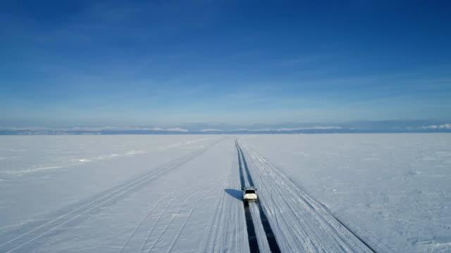 vídeos de stock e filmes b-roll de white suv car moving on the ice of frozen lake baikal - lago baikal