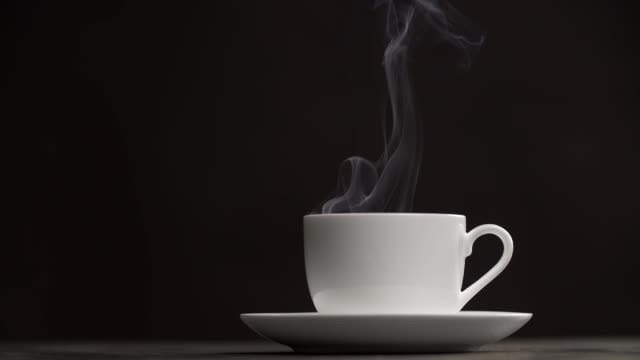 White tea or coffee cup and a saucer on a table against black background. Steam (smoke) is coming out of the cup